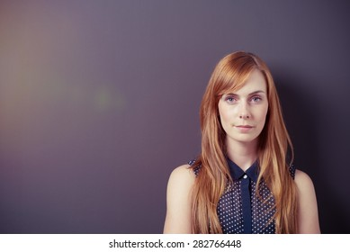 Close up Pretty Blond Lady, in Sleeveless Shirt, Against Gray Wall with Copy Space and Staring at the Camera.