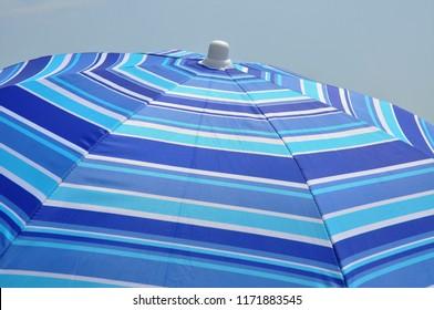 Close up of a Pretty blue striped beach umbrella.