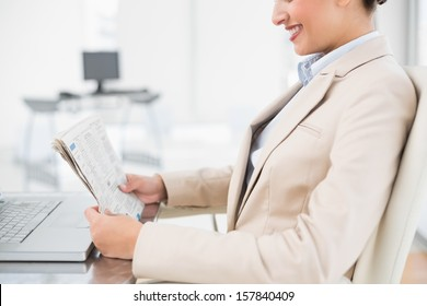 Close up of a pretty businesswoman reading a newspaper in bright office
