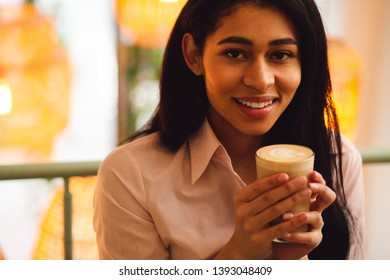 Close up of a pretty dark haired lady smiling and holding a glass of delicious coffee drink in her hands