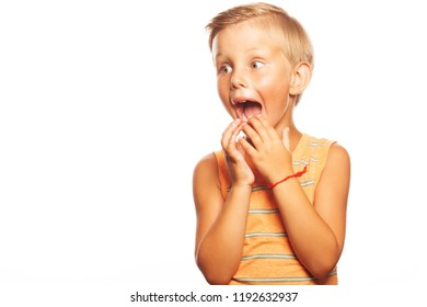 Close up of pretty little boy with blond hair holding hands near his face, screaming loudly, trying to scare friend in school. Copy-space. Studio shot