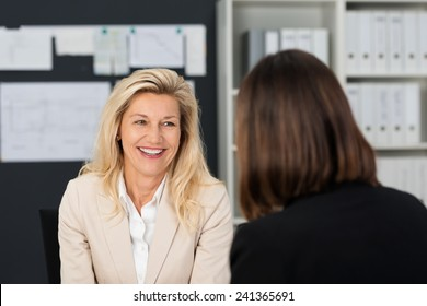 Close up Pretty Smiling Adult Manager Woman Talking to her Subordinate at her Office.