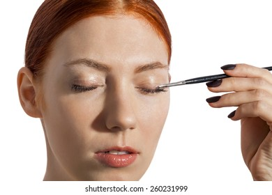 Close up Pretty Woman Applying Eye Shadow Makeup Using Brush on White Background.