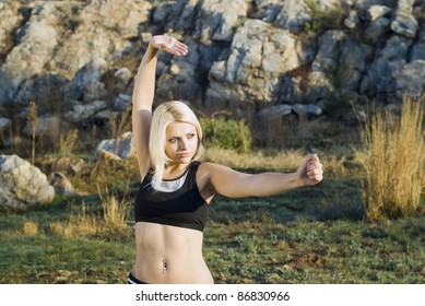 Close up of pretty woman practicing kung fu or tai chi in natural park