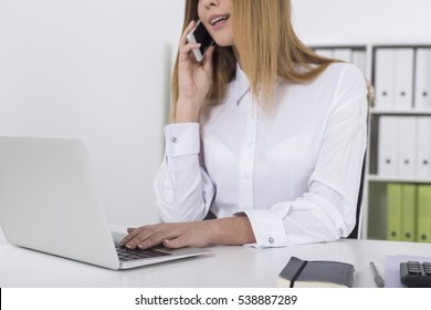 Close up of a pretty young girl on her mobile in a white office with folders on the shelves. Concept of secretary work
