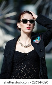 Close up Pretty Young White Woman in Black Trendy Attire with Fashionable Necklace and Shades. Strike an Outdoor Pose