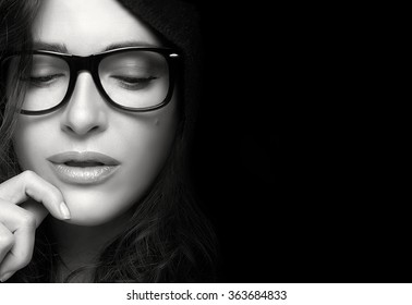 Close up pretty young woman face, with glasses, looking down with one hand on the face. Cool trendy eyewear portrait in black and white with copy space for text