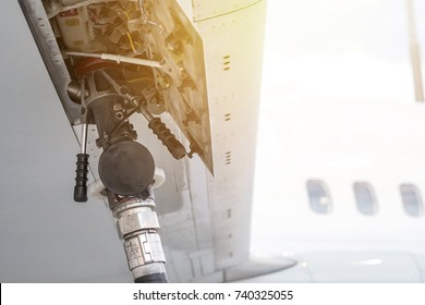 Close up process of refueling commercial aircraft  at airport and fuel host inserted in the aircraft wing
