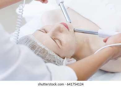 Close up of professional beautician hands touching female forehead with the equipment for Microcurrents. Cosmetology and beauty concept. Spa clinic receiving stimulating electric facial from therapist