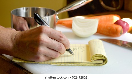 Close up of a professional chef's hand, writing a mise en place food prep list on a yellow notepad to stay organized in preparing a meal.  Vegetables and kitchen tools in the background.