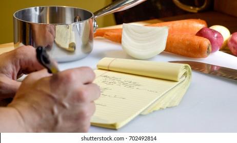 Gros plan sur la main d'un cuisinier professionnel, écrivant une liste de préparation de nourriture mise en place sur un bloc-notes jaune pour rester organisé pour préparer un repas.  Légumes et outils de cuisine en arrière-plan.