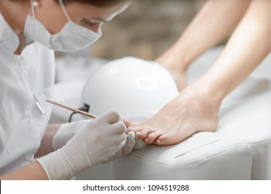 Close up of professional cleaning cuticle around nails on feet, with wooden stick. Female specialist in mask on face, making pedicure for client with uv lamp near. Beauty salon and service.