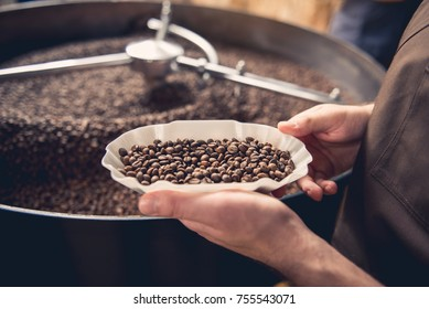 Close up professional coffee roaster holding bowl with beans. Control concept