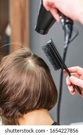 Close up of professional hairdresser is drying female hair, back view.