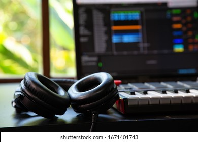 Close up of professional headphones and a Midi keyboard in a music producer home studio. Laptop and window with nature in the background.