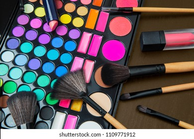 Close up of professional makeup equipment with a colorful eyeshadow and assorted brushes on the table