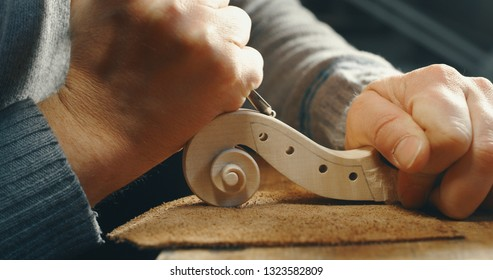 Close up of professional master artisan luthier painstaking detailed work on wood violin in a workshop.