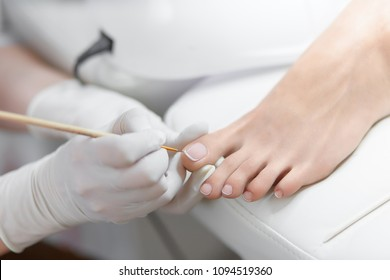 Close up of professional painting by white and glossy acrilyc paint nails on foot. Specialist in beauty salon making french pedicure for female client. Relaxing at beauty salon, caring about nails.