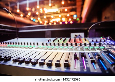 Close up of a professional recording mixer desk, concert with lights in the blurry background