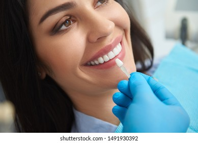Close up of professional stomatologist holding dental crown for female patient