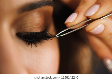 Close up of professional stylist lengthening lashes for female client in a beauty salon.