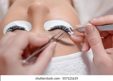 Close up of professional stylist lengthening lashes for female client in a beauty salon. Making permanent make up for woman and eyelash extension procedure special instruments. View from above.