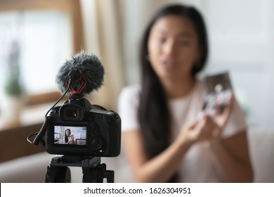 Close up of professional video camera shooting young Asian beauty blogger make unpacking product at home, camcorder device record millennial influencer or vlogger broadcast advertising content