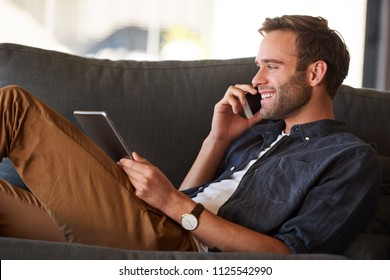 Close up profile image of young attractive caucasian man smiling while talking on the phone and holding a tablet in his other hand while dressed with a great fasion sense and a stylish watch.