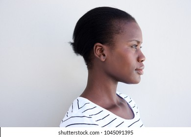 Close up profile image of young black woman against white wall