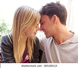 Close up profile portrait of an attractive young tourist couple on holiday being romantic and kissing while relaxing during a summer break vacation. Love and relationships outdoors.