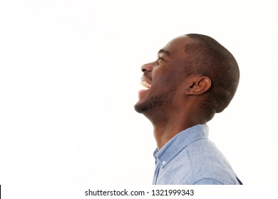 Close up profile portrait of handsome young black man laughing against isolated white background