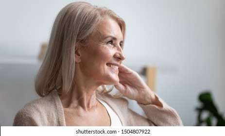 Close up profile portrait smiling mature woman dreaming, thinking about good future, beautiful retired older female with healthy toothy smile looking in distance, feeling satisfied, natural beauty