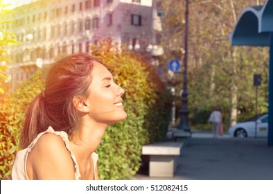 Close up profile portrait of a young beautiful girl smiling with her closing eyes - Outdoor city in the background