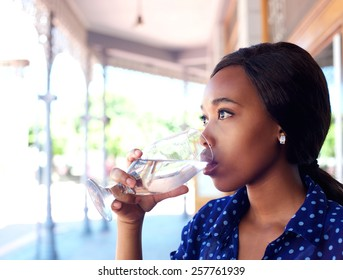 Close up profile portrait of a young business woman drinking water
