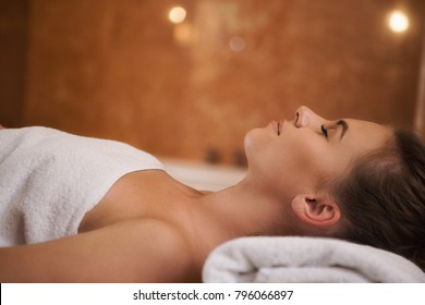 Close up profile shot of a beautiful relaxed young woman lying on the massage table withher eyes closed enjoying pampering treatment at the spa salon copyspace beauty youth therapy hotel