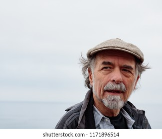 Close up profile of thoughtful senior man with a gray beard wearing a cap gazing into distance