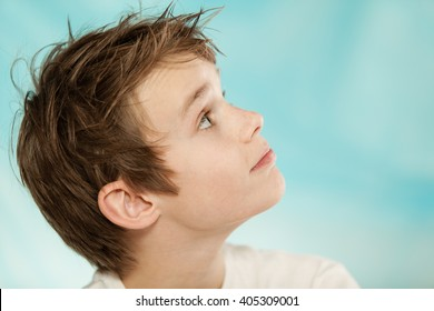 Close up profile view of the head on an eager handsome young boy looking up towards blank blue copy space