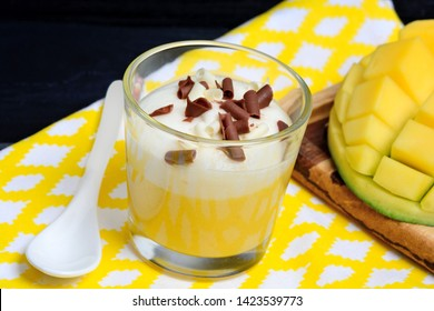 Close up of pudding of mango with whipped cream and chocolate in a glass jar on towel