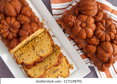 Close up of pumpkin bread on white plate shot from above with uncut loaf on side sitting on orange striped towel