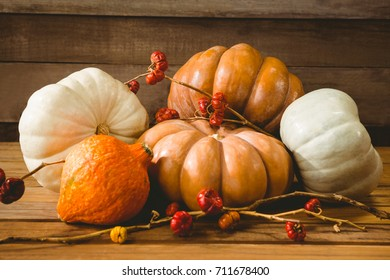 Close up of pumpkins with plant stems on wooden table