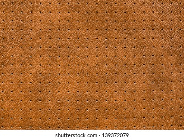 Close up of punched tan leather background.
