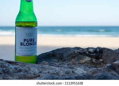 Close up of Pure blond lager beer on volcanic rock in a blurry beach background at Cabarita beach, New South Wales, Australia. Editorial. Taken on February 12th, 2018.