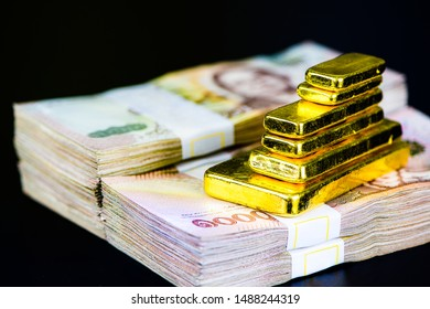 close up pure gold bar ingot put on pile one thousand baht banknotes black color surface background represent the business and finance concept idea, Real gold bars background.
