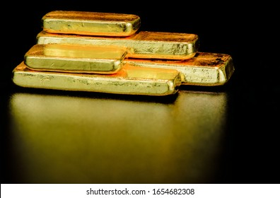 Close up pure gold bar ingot put on the black color surface background represent the business and finance concept idea.Gold investing club investment resources technical analysis news gold prices
