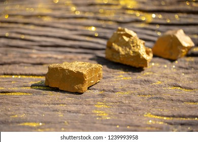 close up pure gold minerals with golden light on old wooder background, investment and business concept