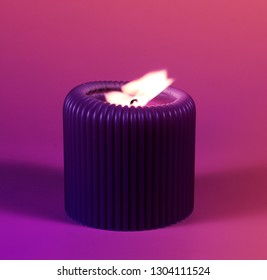 Close up of purple cande glowing with bright flame on gradient background. Decoration for St. Valentine's day in gorgeous neon colors.  Romantic and relaxing atmosphere created by the candelight.