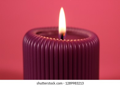 Close up of purple cande glowing with calm flame on bright pink background. Decoration for St. Valentine's day in gorgeous neon colors.  Romantic and relaxing atmosphere created by the candelight.