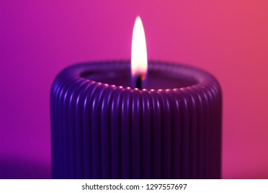 Close up of purple cande glowing with calm flame on pink background. Decoration for St. Valentine's day in gorgeous neon colors.  Romantic and relaxing atmosphere created by the candelight.