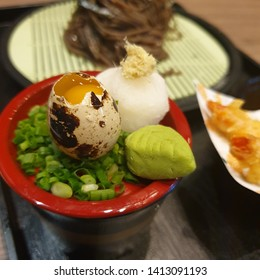 close quail egg in manu soba noodles and tempura