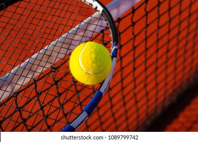 Close up of a racquet with a tennis ball on a red clay court.